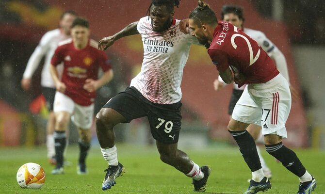 Kessie y Telles luchan por el balón. Revisa las mejores cuotas para el Milan vs Manchester United